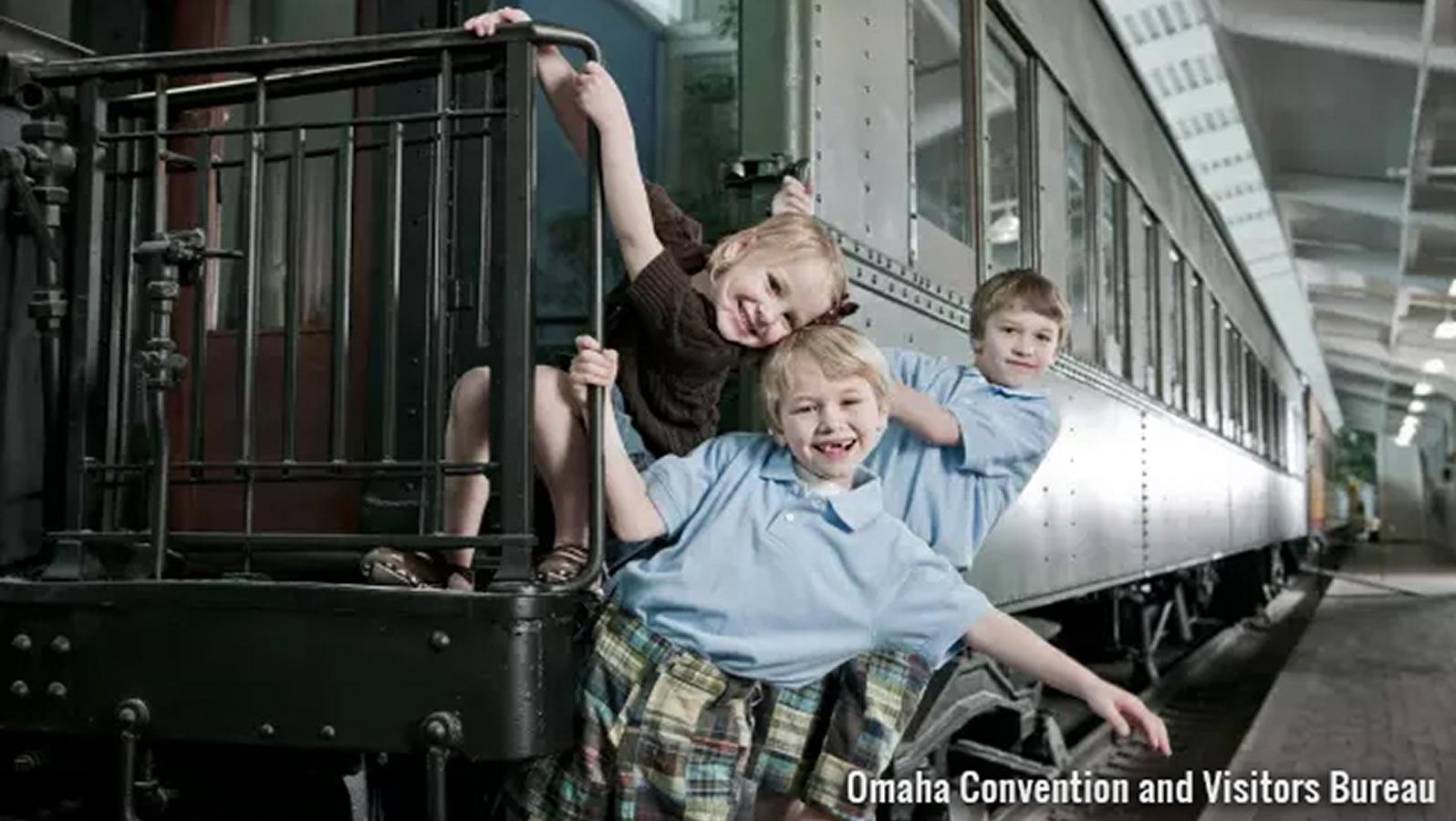 Children smiling on a train railing