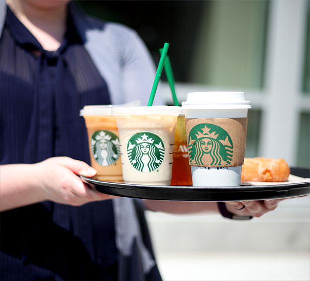 Barista holding a tray of Starbucks drinks