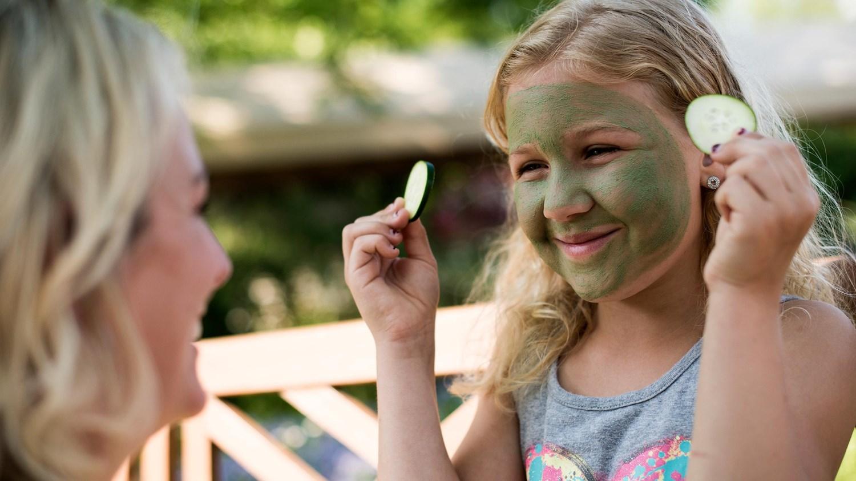 A little girl having fun with a facial mask