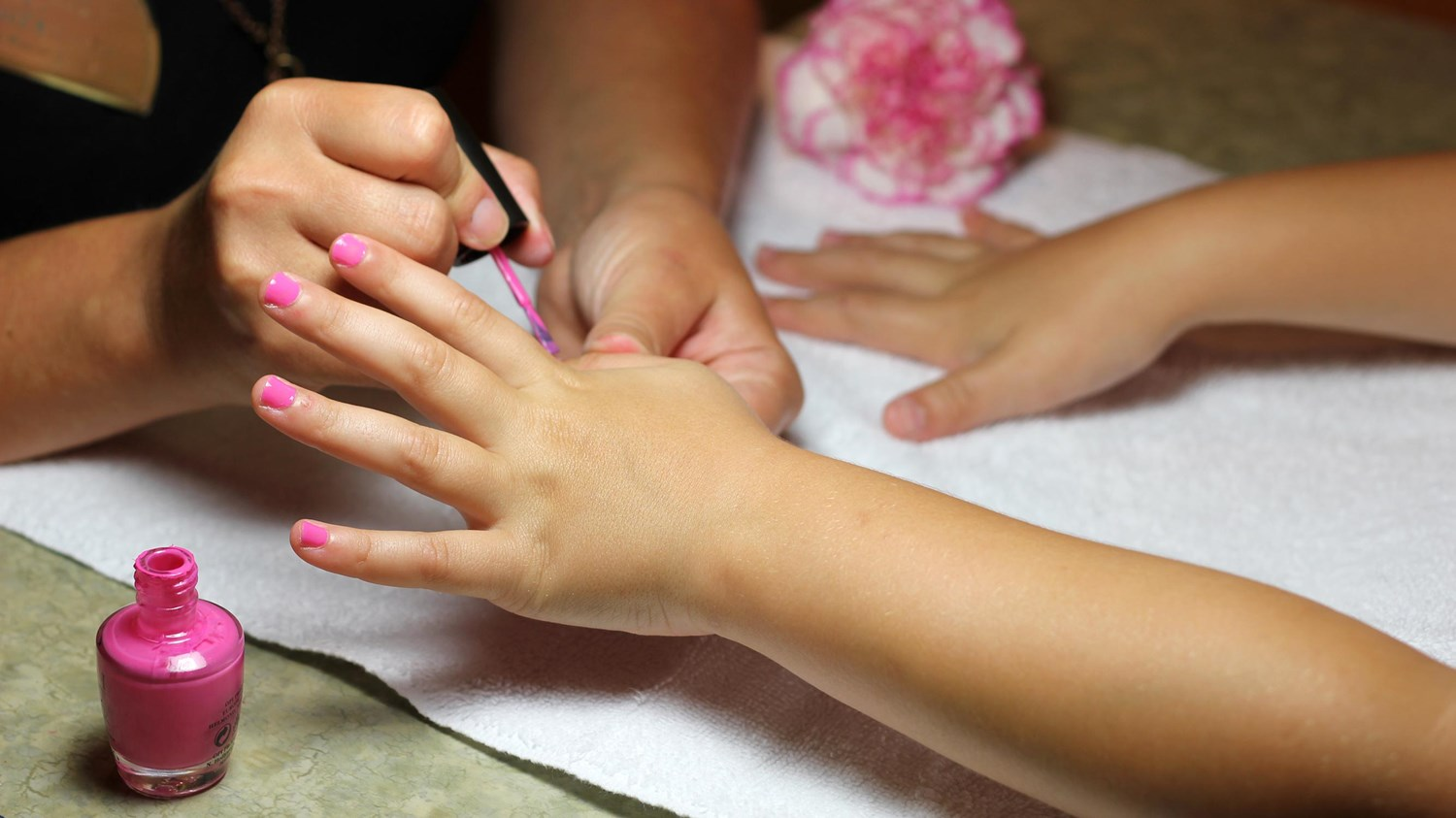 A young girl getting her nails done