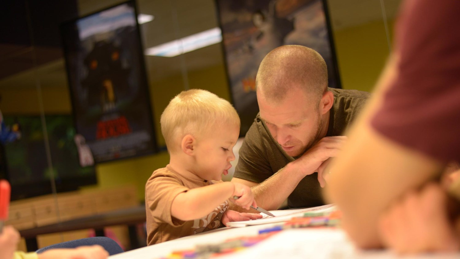Father helping his baby son paint a picture