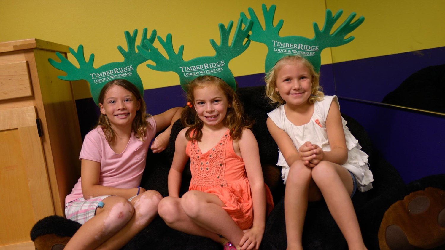 Little girls posing with their moose antler crowns