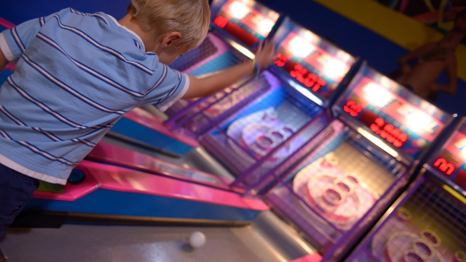 A boy playing skeeball in the arcade
