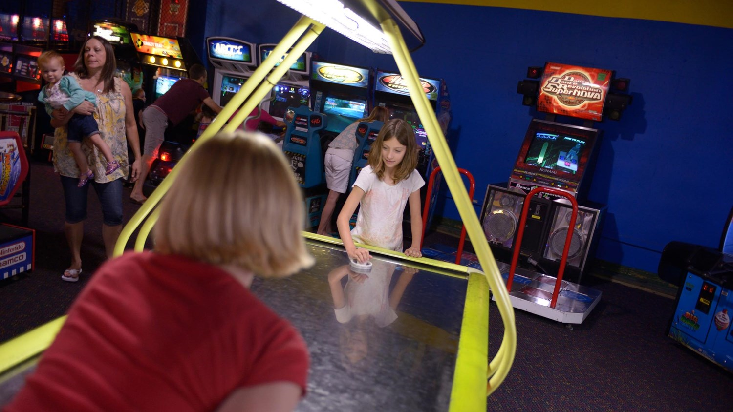 A couple girls playing air hockey