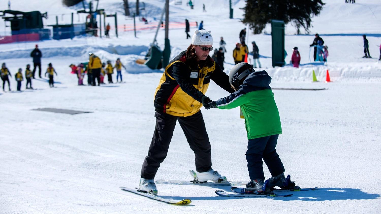 Ski Instructor teaching a boy to ski