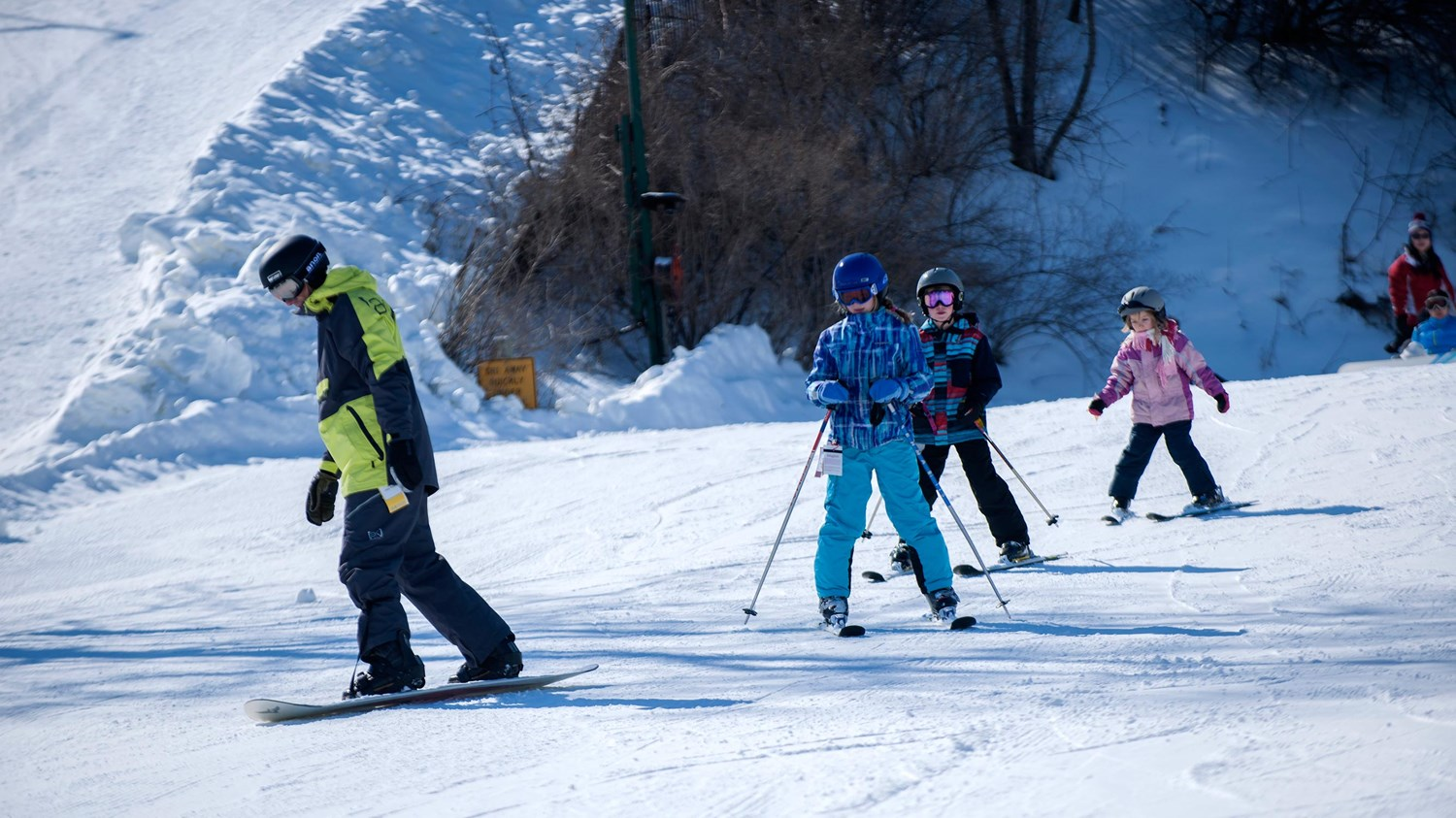 Kids skiing and snowboarding down the slope