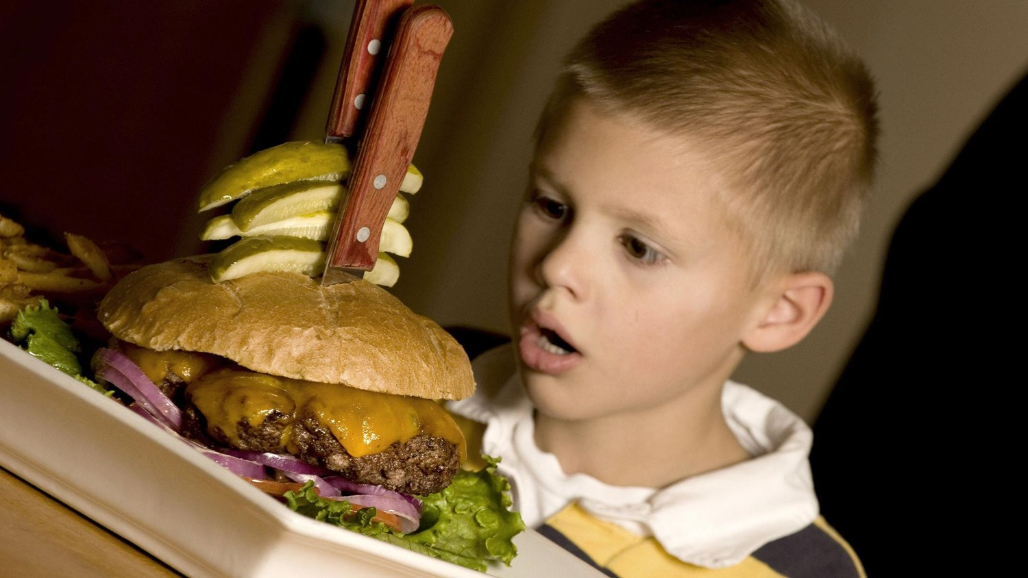Boy with a surprising look gazing at the big cheeseburger